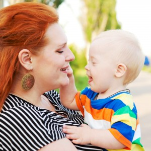 mother and baby with Down syndrome smiling, hugging and talking